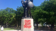 A Confederate statue with Black Lives Matter spray painted overtop it.